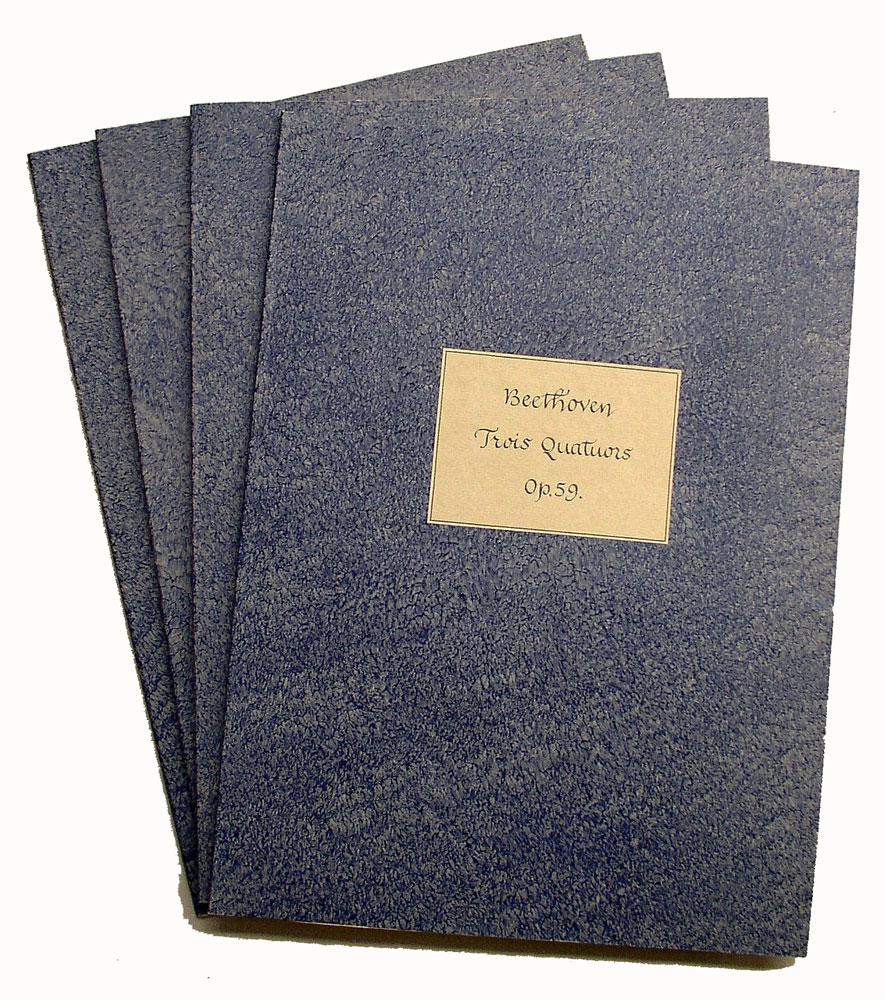 A set of four music parts by Beethoven bound in pastepaper wrappers.
