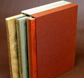 Triple slipcase to house three volumes with cloth of each compartment matching the color of the the respective book