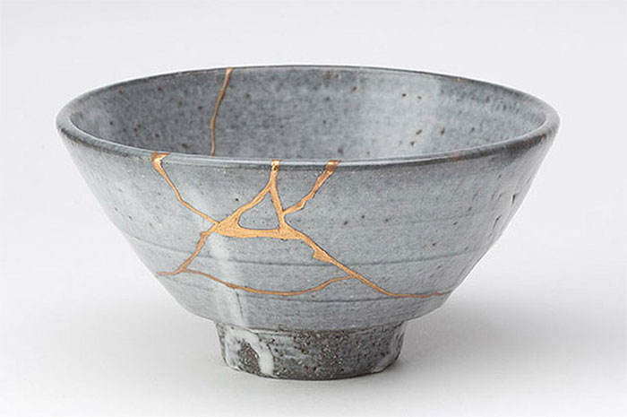 Japanese kintsugi ceramic repair. The adhesive has been dusted with gold powder to highlight the repairs.